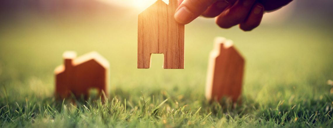 hand-of-woman-choosing-mini-wood-house-model-on-green-grass-planning-buy-real-estate-eco-house-icon-concept