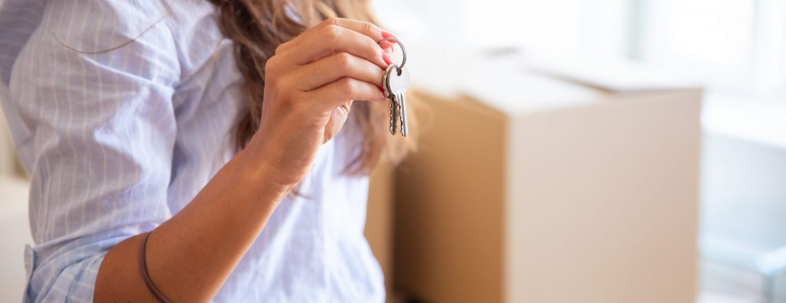 Young woman showing or giving key, posing in new apartment with heap of carton boxes in background. Cropped shot, closeup. Property buying or mortgage concept
